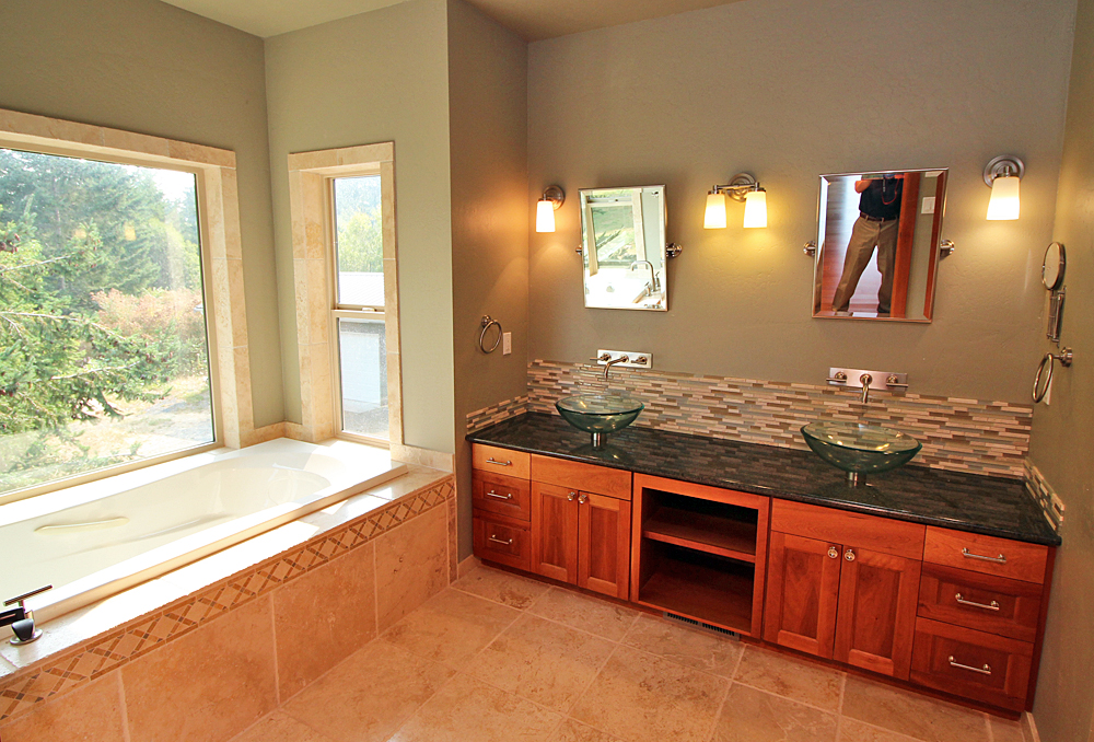 Bathroom with wood cabinets, glass sinks, and custom tiling.