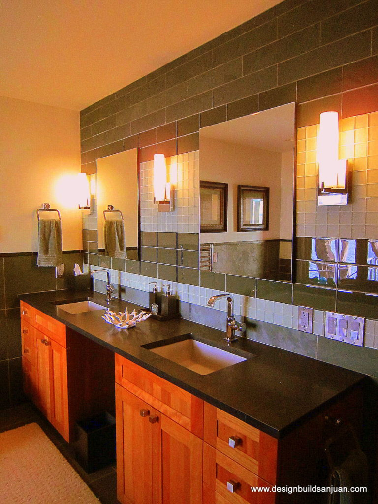 Bathroom featuring two sinks and a green tile wall behind them.