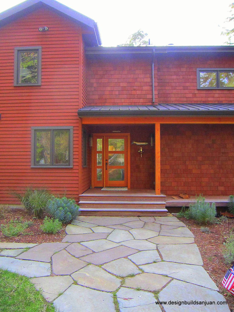 Photo of stone walkway in front leading to a reddish tone waterfront home.