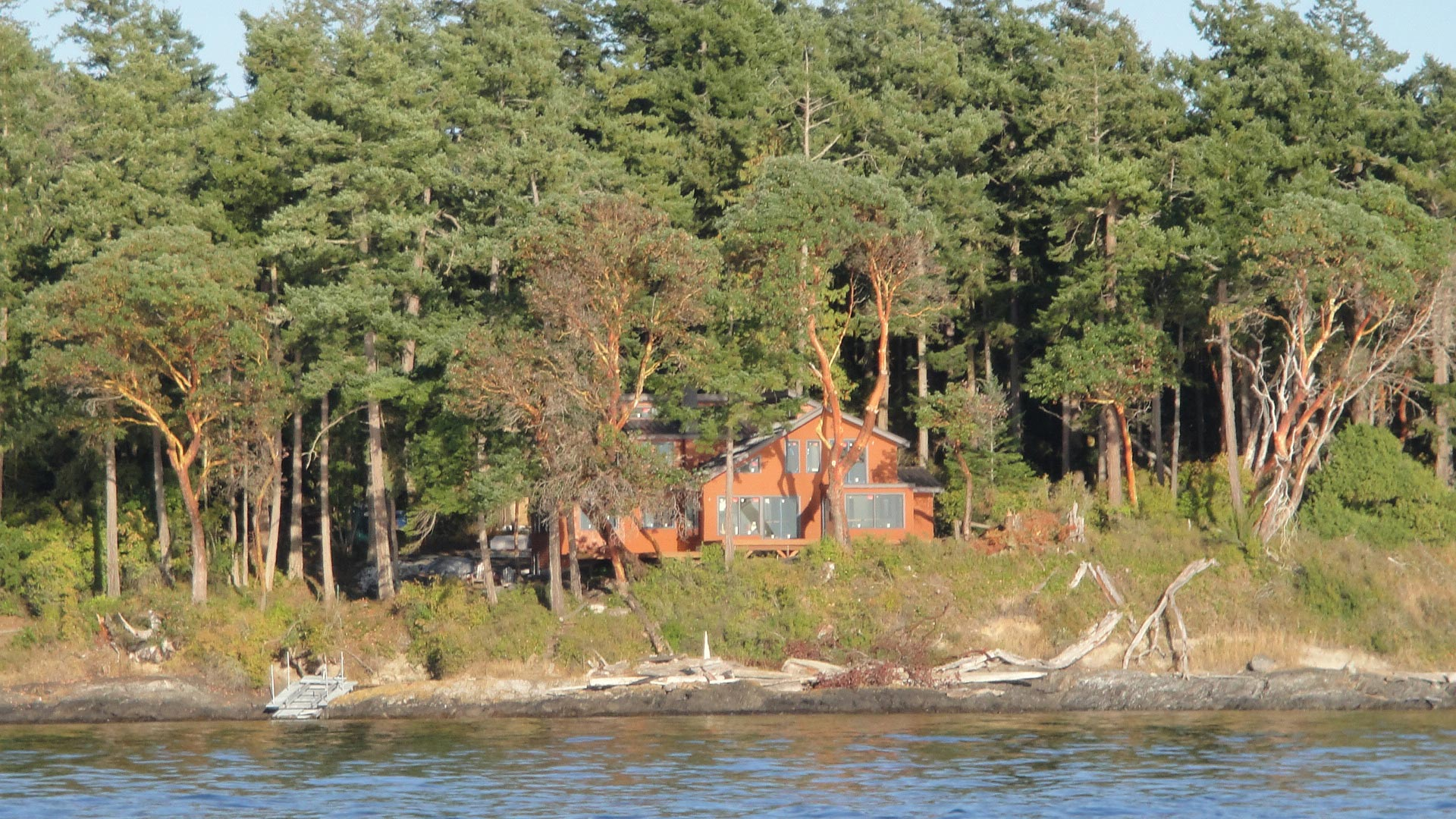 Completed custom home in front of a lake, surrounded by trees.